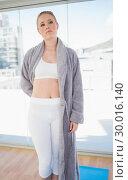 Купить «Serious sporty blonde wearing a bathing gown», фото № 30016140, снято 2 июля 2013 г. (c) Wavebreak Media / Фотобанк Лори
