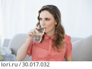 Купить «Beautiful pregnant woman drinking glass of water sitting on couch in living room», фото № 30017032, снято 27 июня 2013 г. (c) Wavebreak Media / Фотобанк Лори