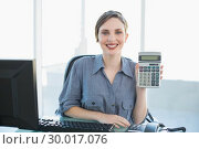 Купить «Joyful young businesswoman showing calculator sitting at her desk», фото № 30017076, снято 27 июня 2013 г. (c) Wavebreak Media / Фотобанк Лори