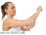 Купить «Suffering young woman touching her sore elbow», фото № 30017240, снято 31 июля 2013 г. (c) Wavebreak Media / Фотобанк Лори