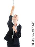 Купить «Serious chic businesswoman pulling a silver chain», фото № 30017524, снято 28 июня 2013 г. (c) Wavebreak Media / Фотобанк Лори