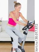Купить «Sporty unsmiling blonde training on exercise bike using tablet», фото № 30017872, снято 28 июня 2013 г. (c) Wavebreak Media / Фотобанк Лори