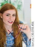 Купить «Smiling redhead biting her reading glasses», фото № 30018456, снято 15 августа 2013 г. (c) Wavebreak Media / Фотобанк Лори