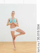 Купить «Calm slim blonde standing in eagle pose», фото № 30019504, снято 11 июля 2013 г. (c) Wavebreak Media / Фотобанк Лори