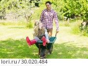 Купить «Happy man pushing his laughing girlfriend in a wheelbarrow», фото № 30020484, снято 4 июля 2013 г. (c) Wavebreak Media / Фотобанк Лори