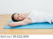 Купить «Smiling young woman lying on exercise mat», фото № 30022604, снято 12 июля 2013 г. (c) Wavebreak Media / Фотобанк Лори