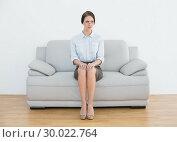 Купить «Full length of a serious well dressed woman on sofa», фото № 30022764, снято 12 июля 2013 г. (c) Wavebreak Media / Фотобанк Лори