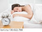 Купить «Woman sleeping in bed with alarm clock in foreground», фото № 30022788, снято 16 июля 2013 г. (c) Wavebreak Media / Фотобанк Лори