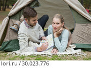 Купить «Young couple lying in tent with a map», фото № 30023776, снято 20 августа 2013 г. (c) Wavebreak Media / Фотобанк Лори