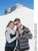 Couple in warm clothing in front of snowed hill. Стоковое фото, агентство Wavebreak Media / Фотобанк Лори
