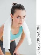 Купить «Tired woman with towel around neck at fitness studio», фото № 30024704, снято 23 июля 2013 г. (c) Wavebreak Media / Фотобанк Лори