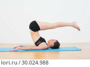 Купить «Fit woman doing plough posture in fitness studio», фото № 30024988, снято 24 июля 2013 г. (c) Wavebreak Media / Фотобанк Лори