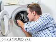 Купить «Technician repairing a washing machine», фото № 30025272, снято 25 июля 2013 г. (c) Wavebreak Media / Фотобанк Лори