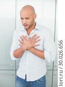 Купить «Casual young man with chest pain at home», фото № 30026656, снято 1 августа 2013 г. (c) Wavebreak Media / Фотобанк Лори