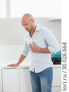 Купить «Casual man suffering from chest pain at home», фото № 30026664, снято 1 августа 2013 г. (c) Wavebreak Media / Фотобанк Лори