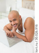 Купить «Smiling casual bald man using laptop in bed», фото № 30026916, снято 1 августа 2013 г. (c) Wavebreak Media / Фотобанк Лори