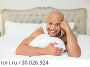 Купить «Smiling casual bald young man lying in bed», фото № 30026924, снято 1 августа 2013 г. (c) Wavebreak Media / Фотобанк Лори