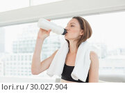 Купить «Woman with towel around neck drinking water in fitness studio», фото № 30027904, снято 7 августа 2013 г. (c) Wavebreak Media / Фотобанк Лори