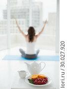 Купить «Woman sitting in meditation posture with healthy food in foreground», фото № 30027920, снято 7 августа 2013 г. (c) Wavebreak Media / Фотобанк Лори