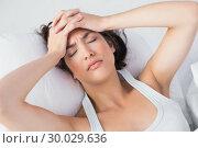 Sleepy woman suffering from headache in bed. Стоковое фото, агентство Wavebreak Media / Фотобанк Лори