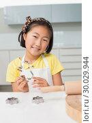 Купить «Smiling young girl holding cookie mold in kitchen», фото № 30029944, снято 29 августа 2013 г. (c) Wavebreak Media / Фотобанк Лори