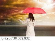 Купить «Composite image of businesswoman holding umbrella», фото № 30032832, снято 2 ноября 2013 г. (c) Wavebreak Media / Фотобанк Лори