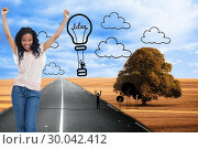 Composite image of a young happy woman stands with her hands in the air. Стоковое фото, агентство Wavebreak Media / Фотобанк Лори