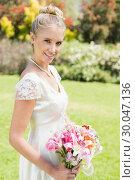 Купить «Pretty blonde bride holding lily bouquet smiling at camera», фото № 30047136, снято 9 октября 2013 г. (c) Wavebreak Media / Фотобанк Лори