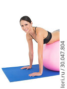 Купить «Portrait of a fit young woman stretching on fitness ball», фото № 30047804, снято 15 октября 2013 г. (c) Wavebreak Media / Фотобанк Лори