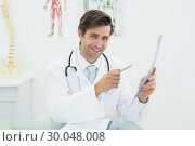 Купить «Portrait of a smiling male doctor with xray», фото № 30048008, снято 2 октября 2013 г. (c) Wavebreak Media / Фотобанк Лори