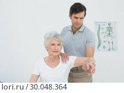 Male physiotherapist stretching a senior womans arm. Стоковое фото, агентство Wavebreak Media / Фотобанк Лори