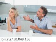 Купить «Couple with coffee cups having a fight in kitchen», фото № 30049136, снято 17 октября 2013 г. (c) Wavebreak Media / Фотобанк Лори