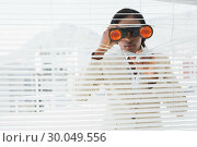 Businessman peeking with binoculars through blinds. Стоковое фото, агентство Wavebreak Media / Фотобанк Лори