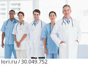 Купить «Portrait of doctors in a row at hospital», фото № 30049752, снято 3 ноября 2013 г. (c) Wavebreak Media / Фотобанк Лори