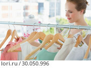 Купить «Smiling female customer at clothing rack in store», фото № 30050996, снято 5 ноября 2013 г. (c) Wavebreak Media / Фотобанк Лори