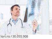 Купить «Serious male doctor examining xray», фото № 30055908, снято 2 ноября 2013 г. (c) Wavebreak Media / Фотобанк Лори
