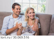 Купить «Relaxed loving couple with coffee cups in living room», фото № 30069516, снято 5 декабря 2013 г. (c) Wavebreak Media / Фотобанк Лори
