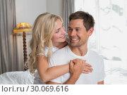 Купить «Loving woman embracing man from behind at home», фото № 30069616, снято 5 декабря 2013 г. (c) Wavebreak Media / Фотобанк Лори