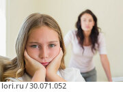 Купить «Sad girl with mother in background», фото № 30071052, снято 18 декабря 2013 г. (c) Wavebreak Media / Фотобанк Лори