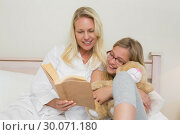 Купить «Mother and daughter reading novel in bed », фото № 30071180, снято 18 декабря 2013 г. (c) Wavebreak Media / Фотобанк Лори