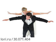 Купить «Happy groom with arms outstretched carrying bride on back», фото № 30071404, снято 8 октября 2013 г. (c) Wavebreak Media / Фотобанк Лори