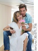 Купить «Portrait of a loving couple with flowers», фото № 30071716, снято 17 декабря 2013 г. (c) Wavebreak Media / Фотобанк Лори