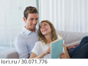 Купить «Young couple reading book on couch», фото № 30071776, снято 17 декабря 2013 г. (c) Wavebreak Media / Фотобанк Лори
