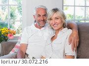 Купить «Smiling mature couple sitting on sofa in living room», фото № 30072216, снято 6 декабря 2013 г. (c) Wavebreak Media / Фотобанк Лори