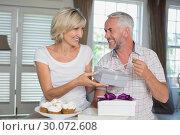 Купить «Happy woman giving a gift box to mature man», фото № 30072608, снято 6 декабря 2013 г. (c) Wavebreak Media / Фотобанк Лори