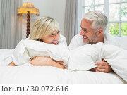 Купить «Happy mature couple lying in bed at home», фото № 30072616, снято 6 декабря 2013 г. (c) Wavebreak Media / Фотобанк Лори
