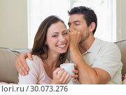 Купить «Man whispering secret into a womans ear in living room», фото № 30073276, снято 12 декабря 2013 г. (c) Wavebreak Media / Фотобанк Лори