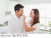 Купить «Loving woman feeding man cucumber slice in kitchen», фото № 30073316, снято 12 декабря 2013 г. (c) Wavebreak Media / Фотобанк Лори