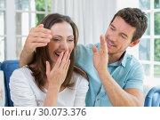 Купить «Close-up of a man surprising woman in living room», фото № 30073376, снято 12 декабря 2013 г. (c) Wavebreak Media / Фотобанк Лори