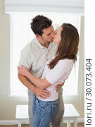 Купить «Loving young couple kissing at home», фото № 30073404, снято 12 декабря 2013 г. (c) Wavebreak Media / Фотобанк Лори